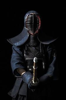 黒の背景に竹刀で日本の剣道ファイター