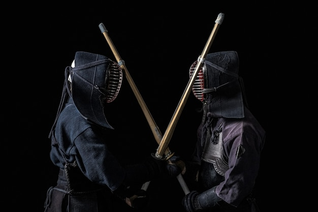 黒の背景に竹刀を持った日本の剣道ファイター