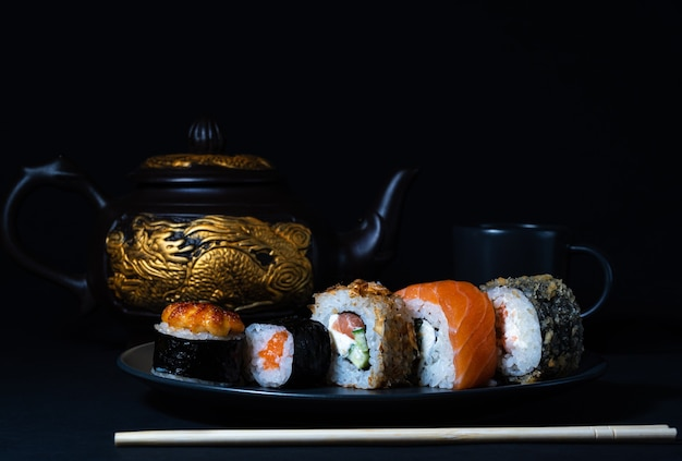 Japanese kitchen set of rolls on a black plate and a teapot with a golden dragon in the background
