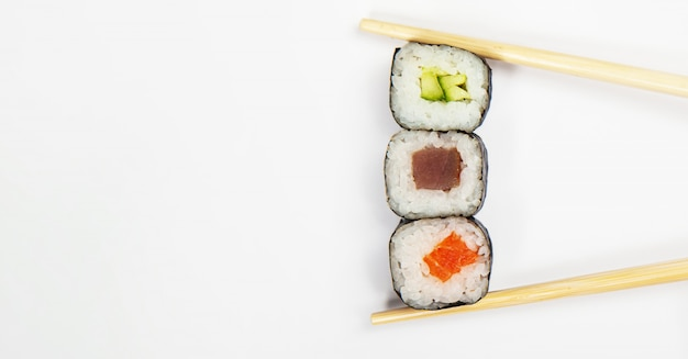 Японская кухня. различные суши и роллы с рыбным сыром и салатом чука в палочках