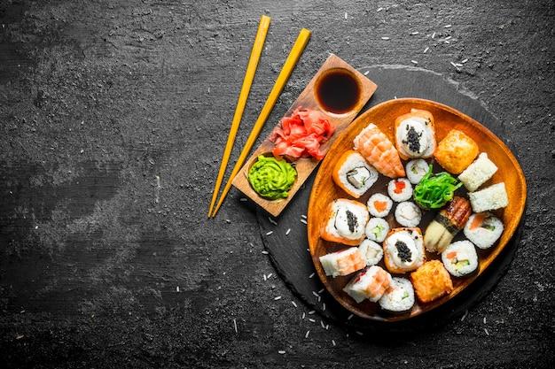 Японские маки, роллы и суши с имбирем, соевым соусом и васаби. на черном деревенском фоне