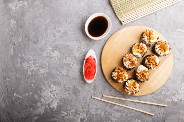 Japanese maki sushi rolls with cream cheese on wooden board on gray concrete