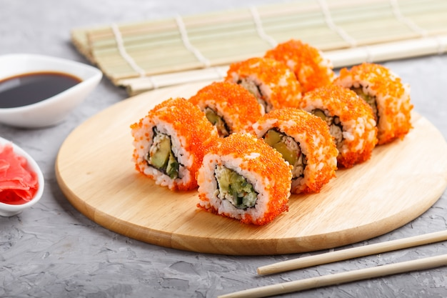 Japanese maki sushi rolls with flying fish roe on wooden board on gray concrete