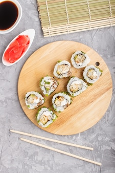 Japanese maki sushi rolls with green onion on wooden board on gray concrete background. top view, close up.