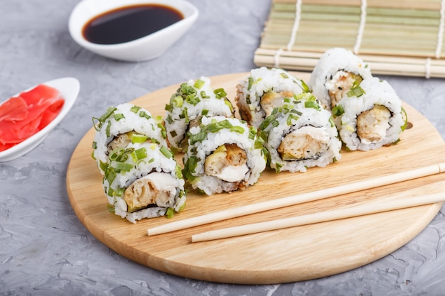 Japanese maki sushi rolls with green onion on wooden board on gray concrete