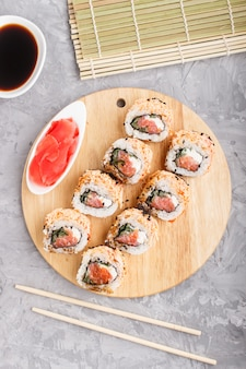 Japanese maki sushi rolls with salmon on a gray concrete background