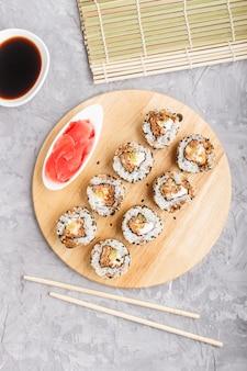 Японские маки суши роллы с лососем, кунжутом, огурцом на деревянной доске на сером фоне бетона. вид сверху.