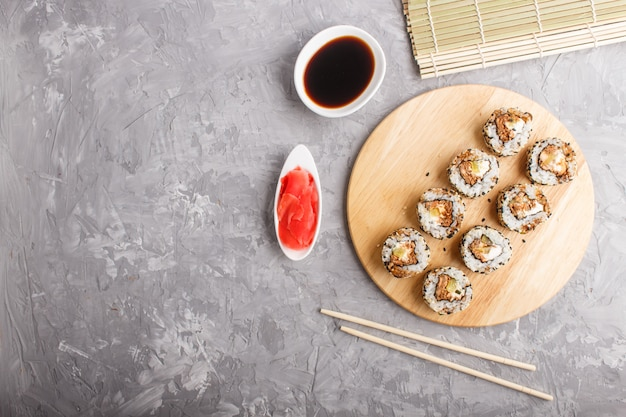 Japanese maki sushi rolls with salmon, sesame, cucumber on wooden board on gray concrete