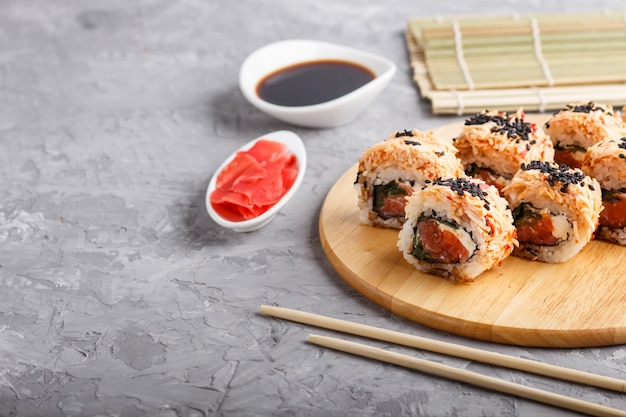 Japanese maki sushi rolls with salmon, sesame, on wooden board on gray concrete