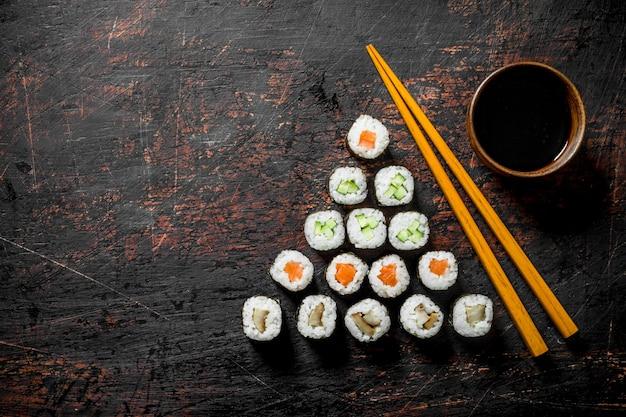 鮭、きゅうり、鶏肉を使った日本の巻き寿司。暗い素朴な背景に