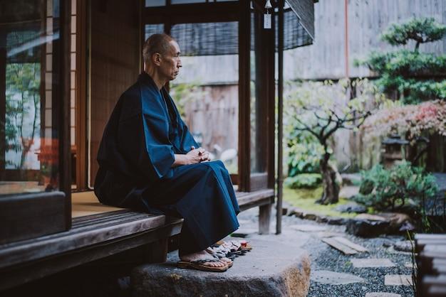 彼の庭で瞑想する日本人男性