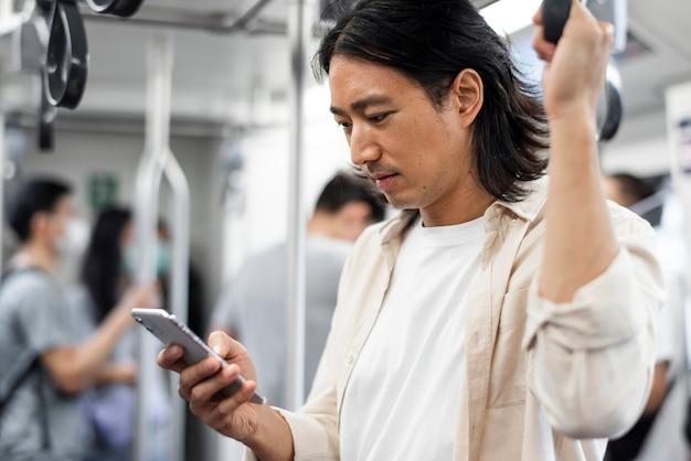 電車の中で彼の携帯電話でスクロールする日本人男性