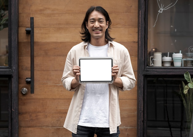 Japanese man showing a digital tablet screen outside his sh