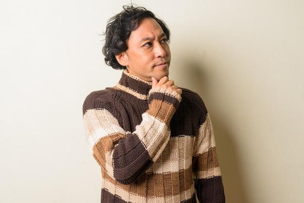 屋内で冬の準備ができている巻き毛の日本人男性