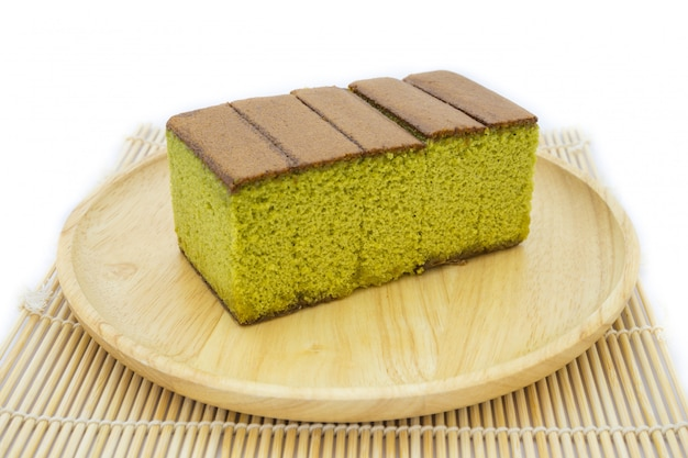 Japanese matcha green tea cake cheesecake on wooden plate and traditional mat isolated