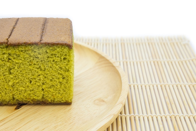 Japanese matcha green tea cake cheesecake on wooden plate and traditional mat