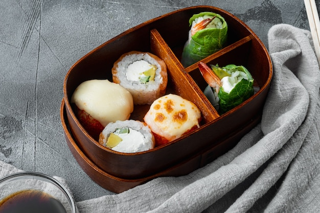 Japanese meal in a box bento with sushi roll eice avocado salmon fish set, on gray stone