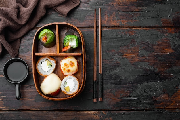 Japanese meal in a box bento with sushi roll eice avocado salmon fish set, on old dark  wooden table