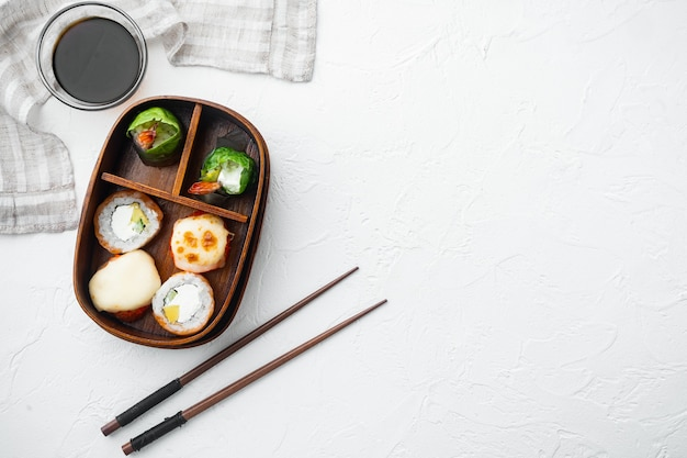 Japanese meal in a box bento with sushi roll eice avocado salmon fish set, on white stone