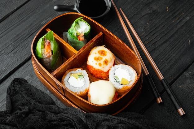 黒い木製のテーブルの背景に、巻き寿司のアイスアボカドサーモンの魚のセットとボックス弁当で日本の食事