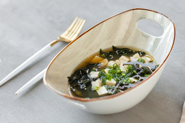 Японский суп мисо в белой миске на столе