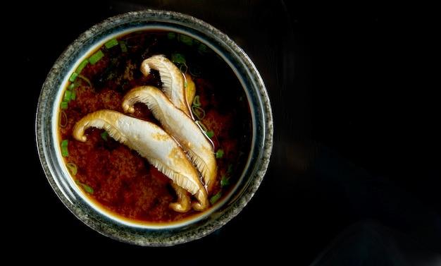 Японский мисо-суп с луком, водорослями и грибами эринги, подается в черной миске