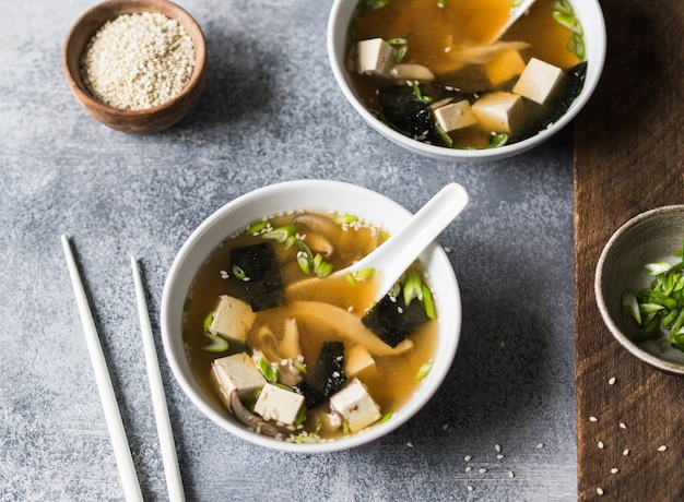 Japanese miso soup with oyster mushrooms in a white bowls with a spoon and white chopsticks on a grey and wood backgrounds.
