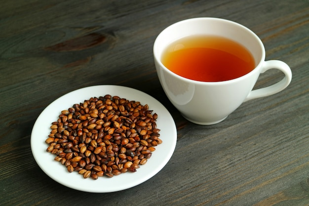 Japanese mugicha or barley tea with a plate of roasted barley on wooden table