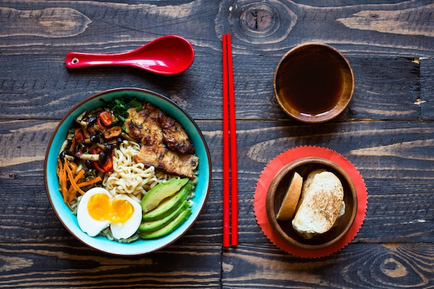 Japanese noodles bowl with chicken, carrots, avocado