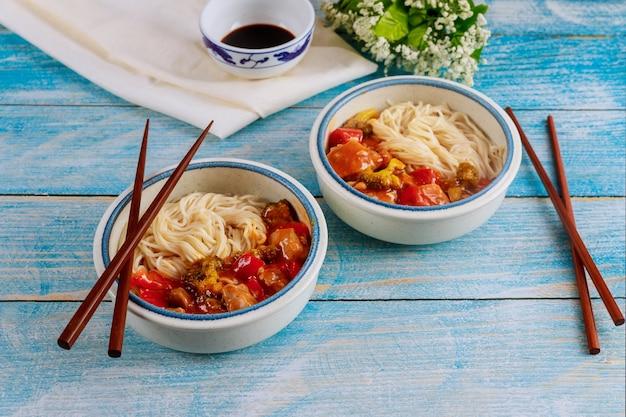 젓가락으로 그릇에 야채 볶음과 일본 국수. 중국 음식.