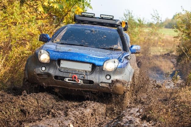 가을 숲에서 깊은 진흙을 통과하는 일본 오프로드 자동차