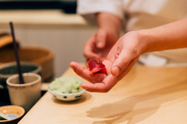Japanese omakase chef making chutoro sushi