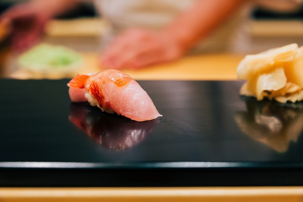 Japanese omakase in edo style close up otoro (fatty tuna) sushi served on glossy black plate.