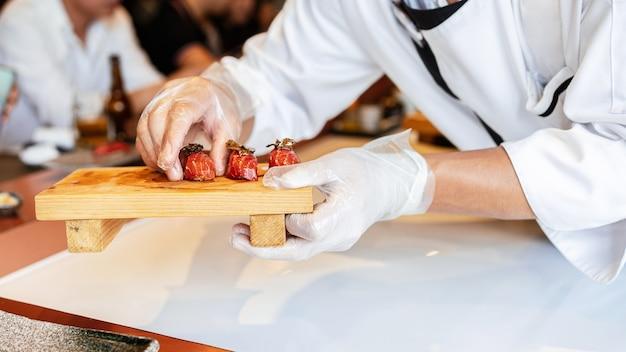 日本のおまかせミール熟成生赤神マグロ寿司にスライスしたトリュフを手で添えます。