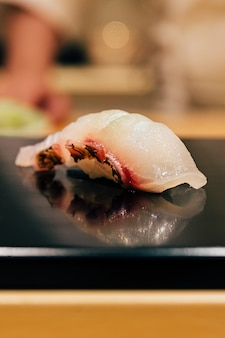 Japanese omakase meal: close up tai (sea bream fish) sushi served on glossy black plate. japanese luxury meal.