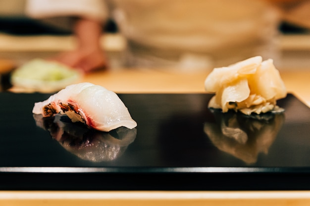 Japanese omakase meal: close up tai (sea bream fish) sushi served on glossy black plate with pickled ginger. japanese luxury meal.