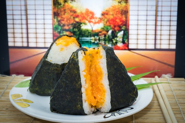 Japanese onigiri sushi on dish and traditional mat with egg shrimp and open door autumn background.