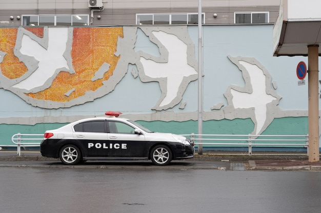 The japanese police car parking beside the wall.