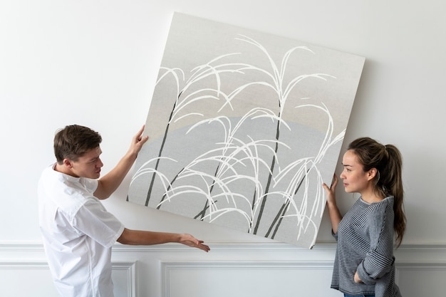 Japanese print on a canvas being hung by a couple