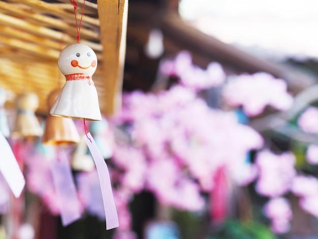Японская дождевая кукла с улыбающимся лицом, нависшей над розовой вишней