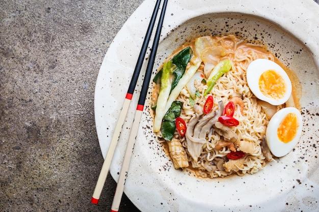 흰 그릇에 닭고기, 표고버섯, 계란을 넣은 일본 라면