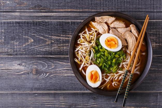 Японский суп рамэн с курицей, яйцом, чесноком и ростками на темном деревянном фоне.