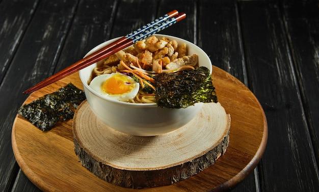 닭고기, 계란, 마늘, 국수와 어두운 나무 배경에 일본라면 수프. 아시아 된장라면.