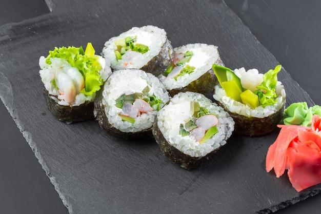 Japanese restaurant, sushi roll on black slate plate