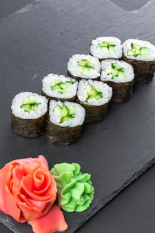 Japanese restaurant, sushi roll on black slate plate. Premium Photo