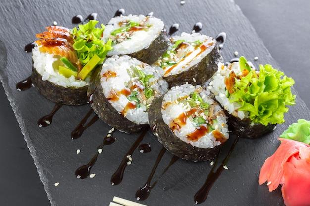 Japanese restaurant, sushi roll on black slate plate.