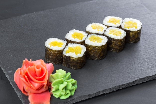 Japanese restaurant, sushi roll on black slate plate.