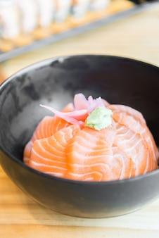 Japanese Rice with salmon sashimi on top in black bowl