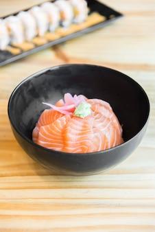 Riso giapponese con sashimi di salmone in cima in ciotola nera