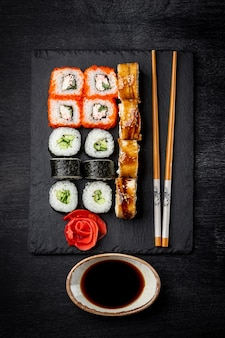 Japanese rolls on black slate board and black background top view